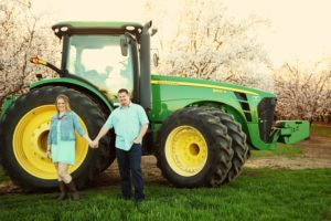 amy and derek in front of tractor in almond orchard